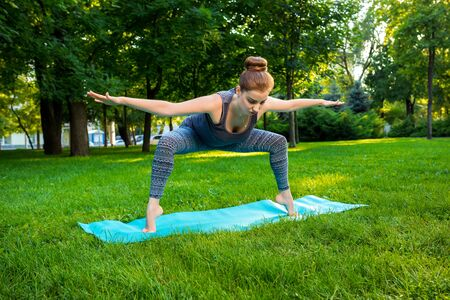 veda: Young fitness woman meditation in a city park.Yoga at sunset in the park. Girl is practicing yoga. Fitness training outdoors. Attractive fitness woman. Workout outdoors. Healthy lifestyle