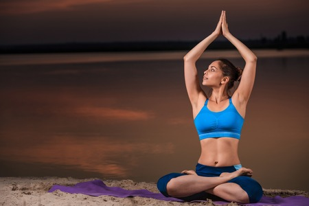 yoga at sunset on the beach. woman doing yoga, performing asanas and enjoying life on the river Stock Photo