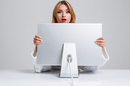 distrustful: young woman sitting in the table and using computer on gray background. Surprised and scared hidden behind the monitor. It peeping from behind him Stock Photo