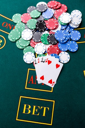 trickery: Poker chips on a poker table at the casino. Closeup. quads, a winning combination. Chips winner