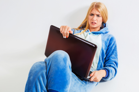 annoyed girl: girl in pajamas with a laptop lying on the floor. studying or doing online shopping. work from home. annoyed, surprised, frowning