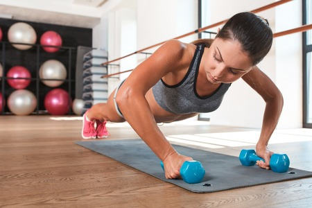 weightlifting gloves: Gorgeous suntanned brunette doing exercises a the gym. girl doing some push ups on a dumbbell