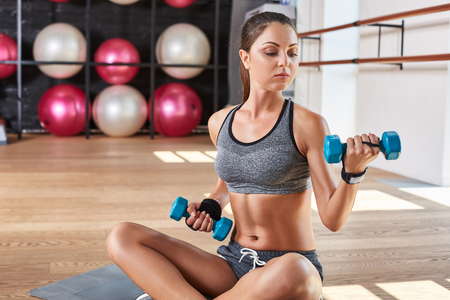Gorgeous suntanned brunette doing exercises a the gym. girl doing lifting dumbbells Stock Photo