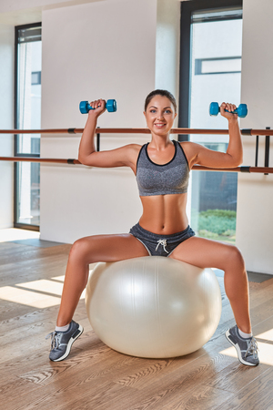 weightlifting gloves: Gorgeous suntanned brunette doing exercises a the gym. girl doing lifting dumbbells on fitball