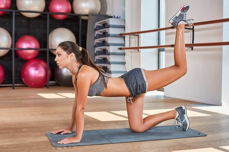 suntanned: Gorgeous suntanned brunette doing exercises a the gym. girl doing stretching on the mat