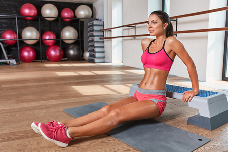weightlifting gloves: Gorgeous suntanned brunette doing exercises a the gym. on the mat Stock Photo