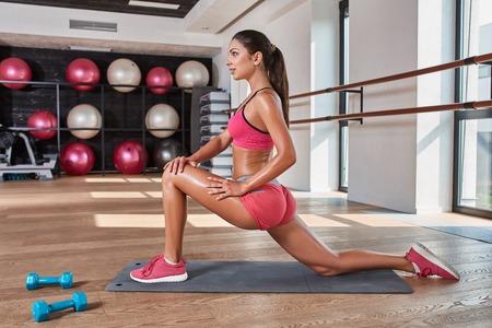 Prachtige suntanned brunette doet oefeningen een de sportschool. meisje doen stretching op de mat Stockfoto