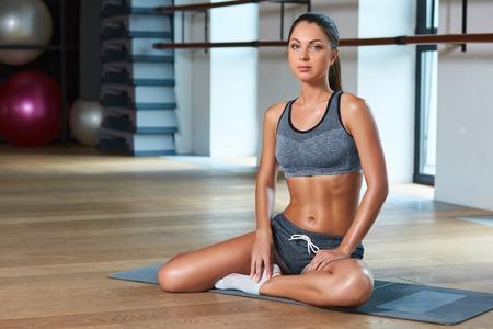suntanned: Gorgeous suntanned brunette doing exercises a the gym. girl sitting on the mat, preparing for sports