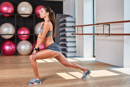 suntanned: Gorgeous suntanned brunette doing exercises a the gym. girl doing stretching