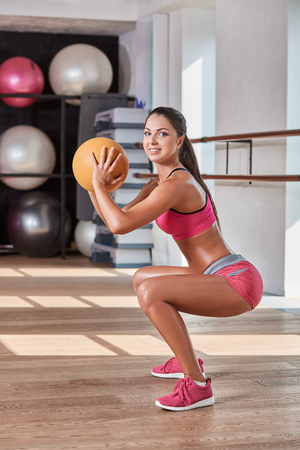 Gorgeous suntanned brunette doing exercises a the gym. girl doing sit-ups with a ball