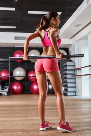 weightlifting gloves: Gorgeous suntanned brunette doing fitness exercises a the gym.