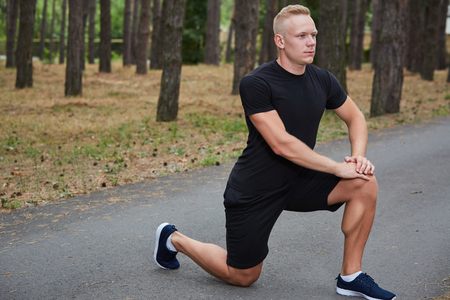 strenght: young athlete running in the forest, doing warm-up and stretching Stock Photo
