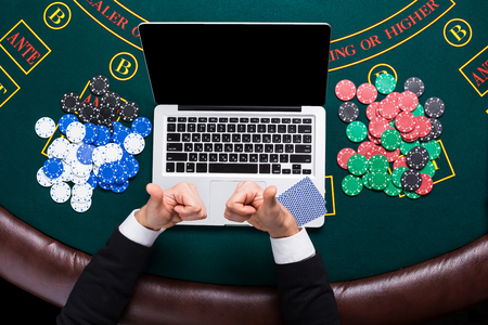casino, online gambling, technology and people concept - close up of poker player with playing cards, laptop and chips at green casino table. top view