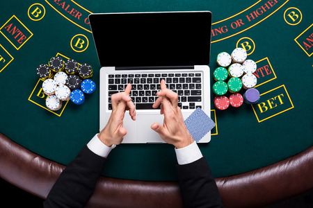 poker player: casino, online gambling, technology and people concept - close up of poker player with playing cards, laptop and chips at green casino table. top view