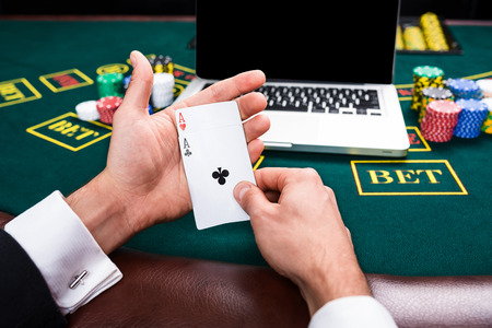casino, online gambling, technology and people concept - close up of poker player with playing cards, notebook and chips at green casino table. first-person view. two aces, a winning combination Stock Photo