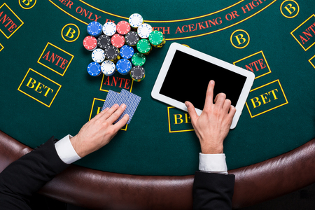 poker player: casino, online gambling, technology and people concept - close up of poker player with playing cards, tablet and chips at green casino table. top view Stock Photo