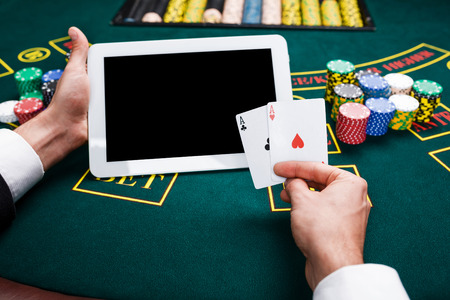 casino, online gambling, technology and people concept - close up of poker player with playing cards, tablet and chips at green casino table. first-person view. two aces, a winning combination Standard-Bild