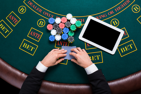 casino, online gambling, technology and people concept - close up of poker player with playing cards, tablet and chips at green casino table. top view Stockfoto