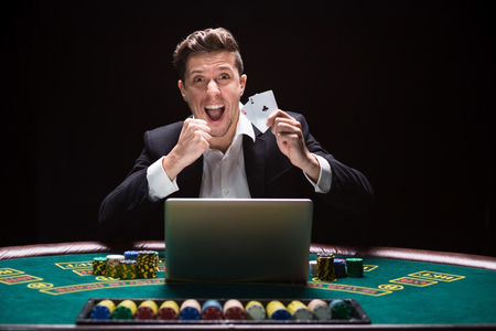 Online poker players sitting at the table. He plays on laptop. he won and is happy, and fool. It shows aces