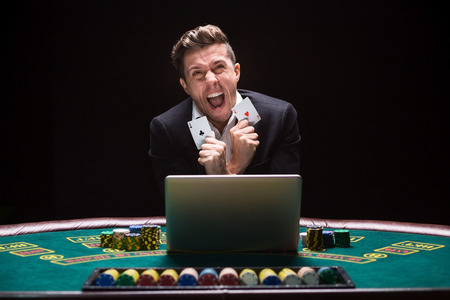 aces: Online poker players sitting at the table. He plays on laptop. he won and is happy, and fool. It shows aces