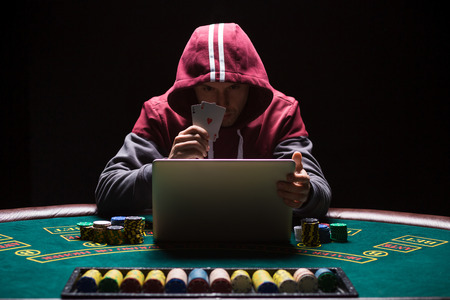 aces: Online poker players sitting at the table. He plays on laptop. The man in the hood, do not see the face. It shows two aces, a winning combination Stock Photo