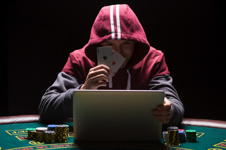 Online poker players sitting at the table. He plays on laptop. The man in the hood, do not see the face. It shows two aces, a winning combination Stock Photo