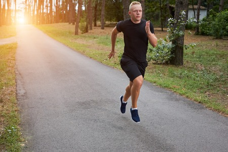 strenght: young athlete running in the forest, motion blur. with a sun flare