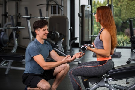 cutie: happy cutie athletic girl , execute exercise with dumb-bells and smile, in sport-hall