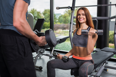 execute: happy cutie athletic girl , execute exercise with dumb-bells and smile, in sport-hall