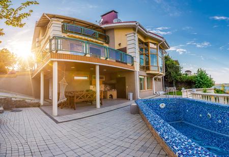 groot landhuis met een zwembad bij zonsondergang