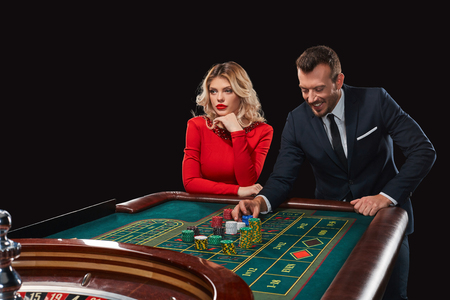 bets: Couple playing roulette wins at the casino. Addiction to the gambling. he bets chips Stock Photo