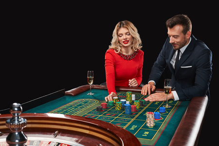 bets: Couple playing roulette wins at the casino. Addiction to the gambling. Girl bets chips Stock Photo