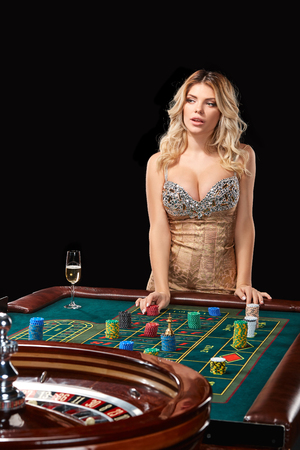 bets: woman in a smart dress plays roulette. addiction to gambling. bets, throwing chips