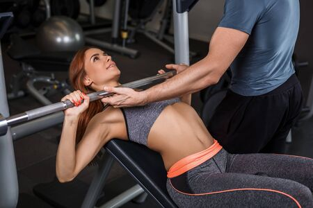 execute: happy cutie athletic girl , with instructor execute exercises barbell and smile, in sport-hall