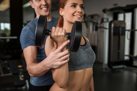 execute: happy cutie athletic girl , with instructor execute exercises with dumbbells and smile, in sport-hall Stock Photo