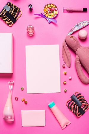 dressy: Flat lay, top view, mock up girls accessories on a pink background. bracelet, rabbit, toy, perfume