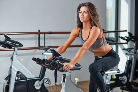 self care: Muscular young woman working out on the exercise bike at the gym, intense cardio workout. She is smiling and looking ahead Stock Photo