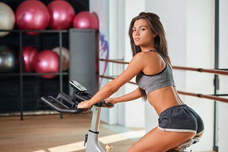 mujer joven muscular que se resuelve en la bicicleta de ejercicio en el gimnasio, una intensa sesión de cardio. Ella está sonriendo y mirando a la cámara