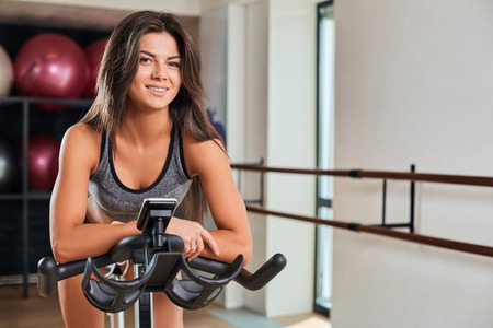 cardio workout: Muscular young woman working out on the exercise bike at the gym, intense cardio workout. She is smiling and looking at the camera