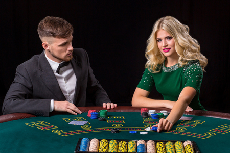 bets: couple playing poker at the table. The blonde girl and a guy in a suit. Woman bets chips