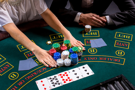 bets: couple playing poker at the table. The blonde girl and a guy in a suit. close up hands. bets all-in