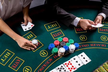 bets: couple playing poker at the table. The blonde girl and a guy in a suit. close up hands. woman bets chips Stock Photo