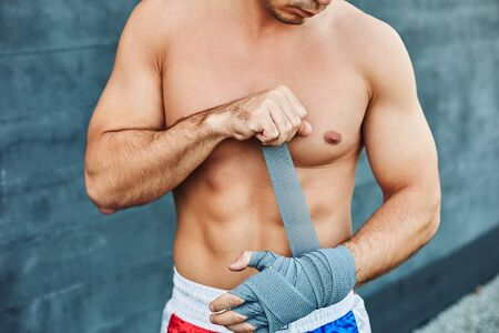 Close up of fit man wearing bandage on his hand. Nude torso Stock Photo