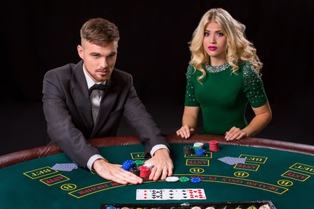 bets: couple playing poker at the green table. The blonde girl and a guy in a suit. all-in bets chips Stock Photo