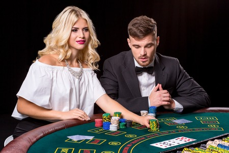 bets: couple playing poker at the green table. The blonde girl and a guy in a suit. chips bets