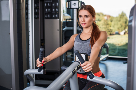 Muscular young brunette doing exercises on the simulator in the gym. She is wearing a gray tracksuit Stock Photo