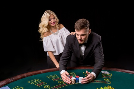 bets: View of young, confident, man with the lady while hes playing poker game. Man bets in poker