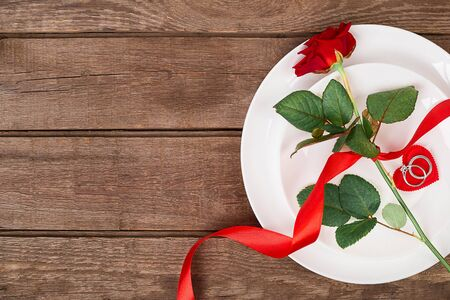 napkin ring: Valentines Day dinner table setting with red ribbon, rose and ring over oak background. Stock Photo