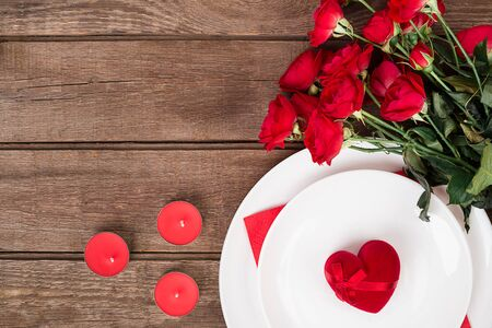napkin ring: Valentines Day dinner table setting with red ribbon, roses, knife and fork  ring over oak background.