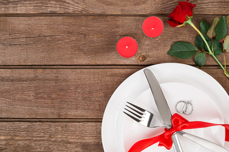 amorousness: Valentines Day dinner table setting with red ribbon, rose, knife and fork  ring over oak background. Stock Photo
